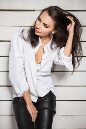 white shirt: Portrait of sexy young woman posing in white shirt and black leather pants Stock Photo