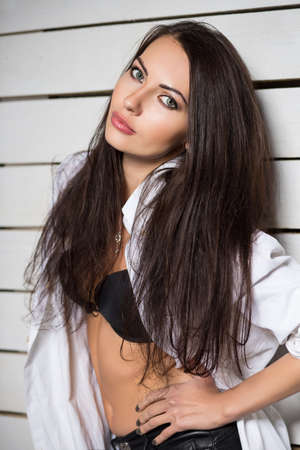seductive women: Portrait of sexy young brunette wearing white shirt and black bra