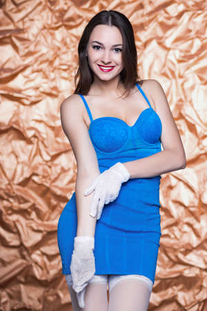 short gloves: Portrait of pretty young brunette posing in blue dress and white gloves Stock Photo
