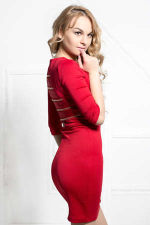 Pretty young blond woman in red dress posing near white wall