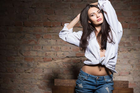 seductive women: Portrait of young sexy woman posing in white shirt and blue jeans