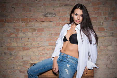 black bra: Young sexy lady posing in black bra, white shirt and blue jeans Stock Photo