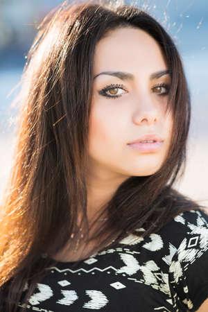Portrait der schönen Brünette mit braunen Augen posiert im Freien