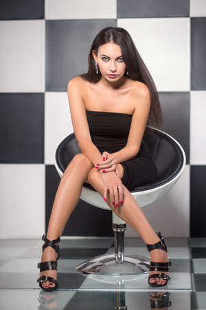 temptress: Alluring young brunette posing on the chair