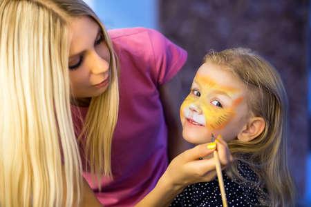 Mooie blonde vrouw het schilderen van het gezicht van een meisje Stockfoto