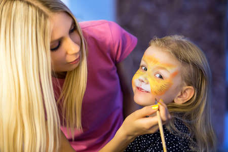 face: Pretty blond woman painting the face of a little girl