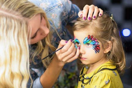 Jonge blonde vrouw het schilderen van het gezicht van een meisje