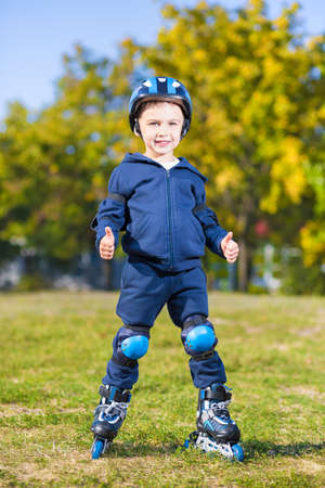 Smiling little skater boy showing two thumb gestures Stock Photo