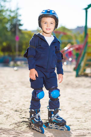 boy skater: Little skater boy in helmet posing on the playground Stock Photo