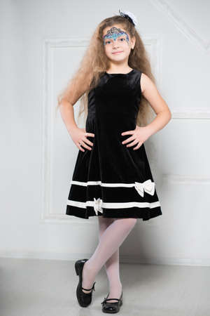 curly hair child: Young girl in black dress with long hair and a pattern on her face