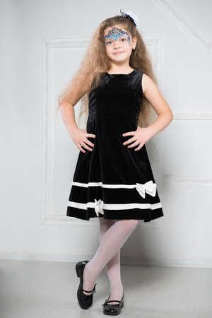 젊은 긴 머리를 가진 검은 드레스 소녀와 그녀의 얼굴에 패턴