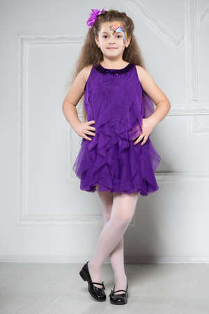 purple dress: Young girl posing in purple dress with painted face