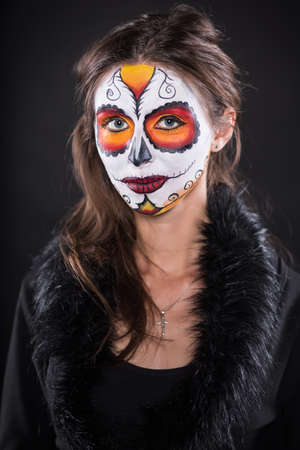 painted face: Portrait of young woman in black clothes with painted face