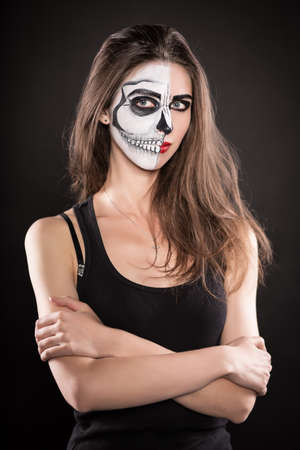painted face: Portrait of pretty brunette with painted face for Halloween