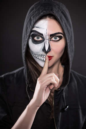 painted face: Portrait of young brunette with painted face for Halloween
