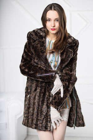 Portrait of young brunette posing in fur coat Stock Photo