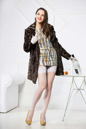 Playful woman wearing short dress and fur coat posing with bottle