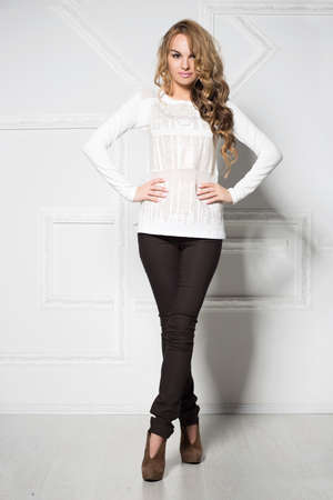black pants: Young smiling woman in black pants and white blouse posing near the wall Stock Photo