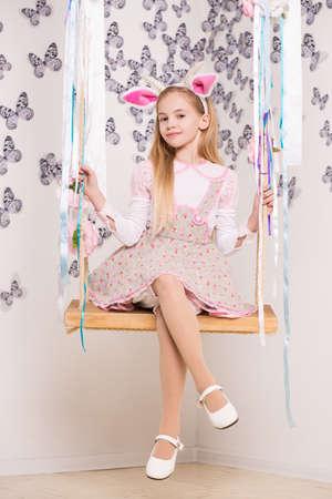 petite fille avec robe: Jolie petite fille en costume de chèvre posant sur la balançoire