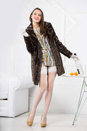 Young playful brunette wearing short dress and fur coat posing with bottle