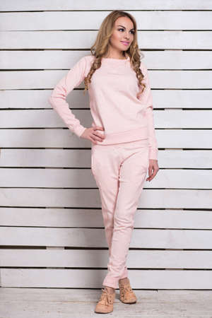 pink posing: Pretty young blond woman in pink clothes posing near white wooden wall