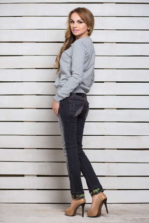 hoody: Pretty woman in gray hoody and black jeans posing near white wooden wall Stock Photo