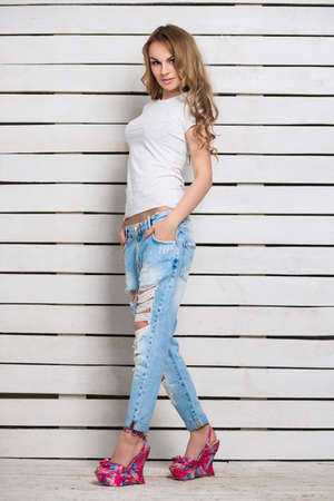 alluring: Alluring blond woman posing in blue ripped jeans and white t-shirt near wooden wall Stock Photo