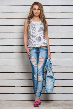 flowered: Attractive young blonde posing in blue ripped jeans and white flowered top Stock Photo