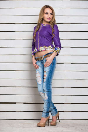 Pensive blond woman in ripped jeans and purple jacket posing near the white wooden wall