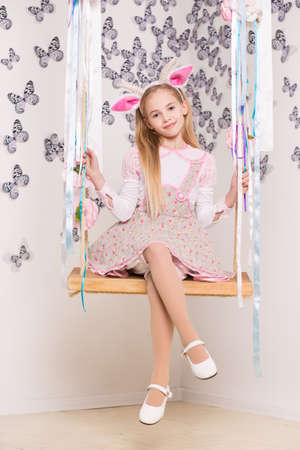Pretty blond girl wearing goat costume posing on the swing Stock Photo