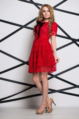 femme blonde Réfléchi posant en robe de dentelle rouge
