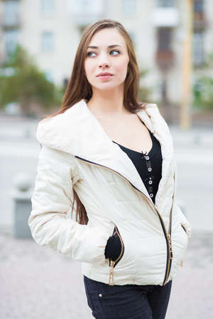 Portrait of thoughtful brunette wearing white jacket posing outdoors
