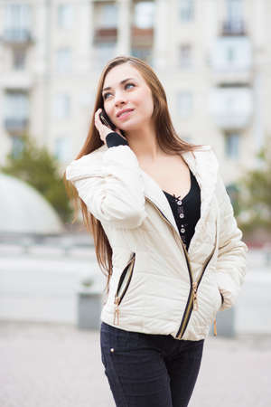 Portrait of smiling brunette wearing white jacket posing with mobile phone outdoors