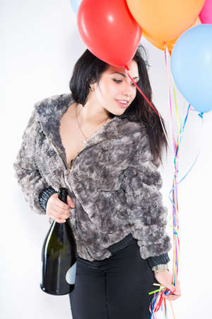 Portrait of sexy brunette wearing furry jacket with a big bottle and balloons