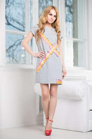 Young beautiful blonde posing in short gray dress near the window Stock Photo