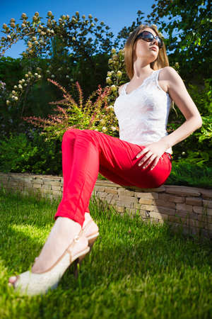 red pants: Pretty blonde woman wearing white top and red pants sitting on the stone fence