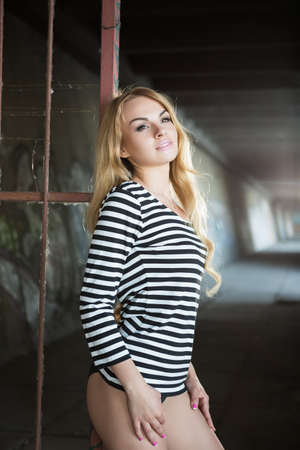 blouse sexy: Sexy thoughtful blond woman in striped blouse posing near iron fence Stock Photo