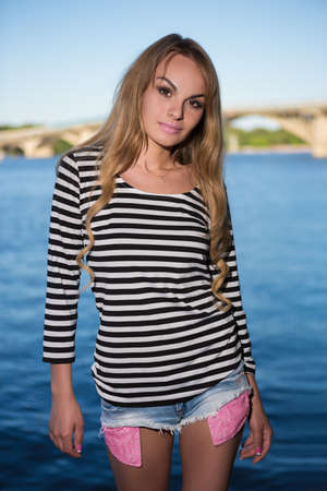 blouse sexy: Young sexy blond woman in striped blouse and shorts posing near the river Stock Photo