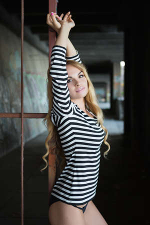 blouse sexy: Sexy young blond woman in striped blouse posing near iron fence Stock Photo