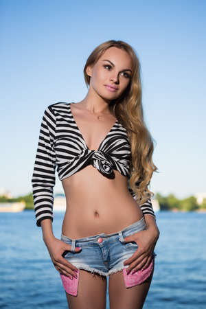 Portrait of sexy slim blond woman in striped blouse and jeans short posing near the river Stock Photo