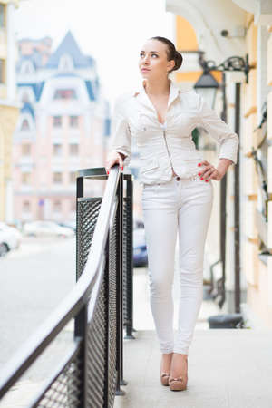 white pants: Thoughtful young woman wearing white pants and jacket posing outdoors