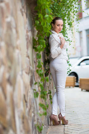 white pants: Playful young woman wearing white pants and jacket posing near the wall