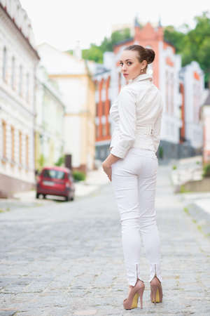 white pants: Alluring young brunette in white pants and jacket posing outdoors