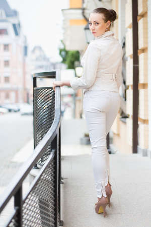 white pants: Beautiful young brunette in white pants and jacket posing outdoors Stock Photo