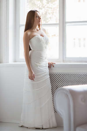 Pretty brunette in white wedding dress posing near the window
