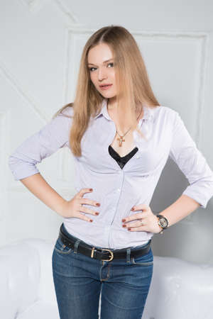 Portrait of beautiful young blonde wearing white shirt and jeans