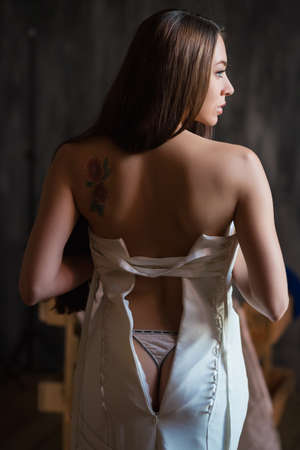 Portrait of sexy young brunette showing her bare back