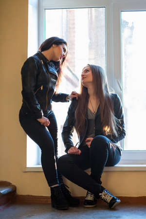 Two girlfriends in casual clothes posing near the window