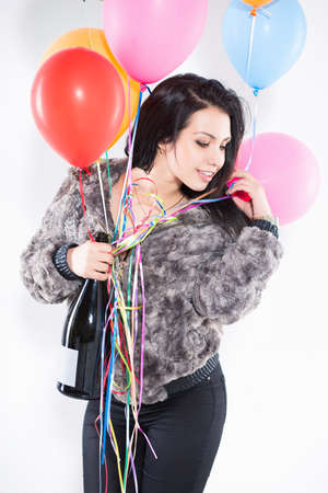 Portrait of smiling brunette with a big bottle and balloons wearing furry jacket