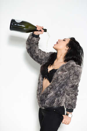 Portrait of sexy brunette pouring herself from a big bottle